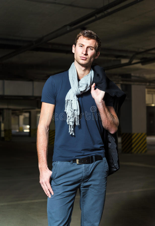 Fashion shot: handsome young man wearing coat and jeans royalty free stock images