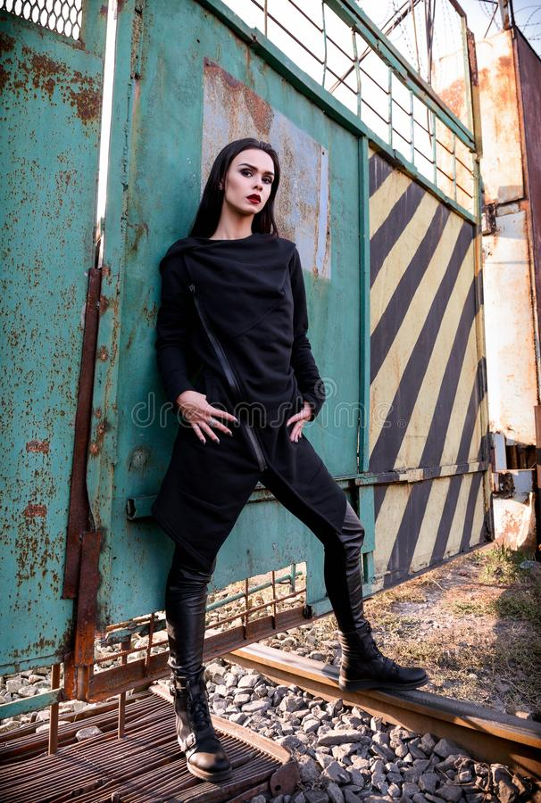 Fashion shot: portrait of beautiful rock girl informal model in tunic and leather pants standing at metallic gates royalty free stock photo