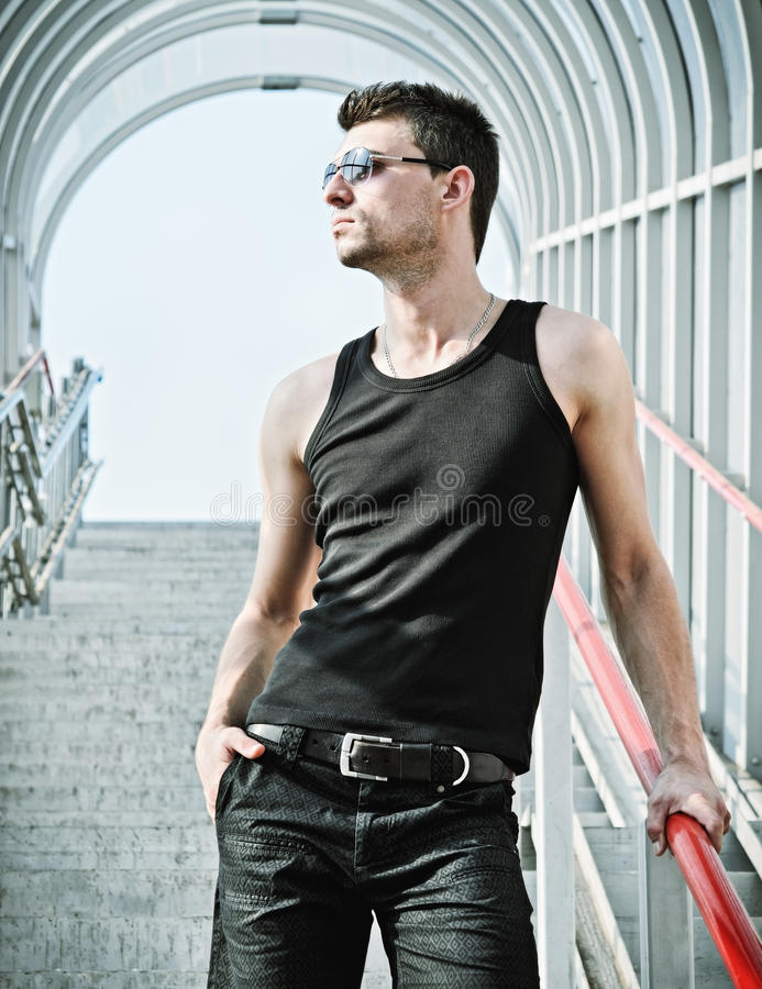 Fashion shot: portrait of handsome young man wearing sunglasses royalty free stock images