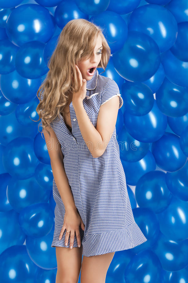 Fashion shot of summer girl in blue,. Blond young happy girl in summer dress with hat taking pose with a lot of blue balloon in background, she looks at right royalty free stock photography