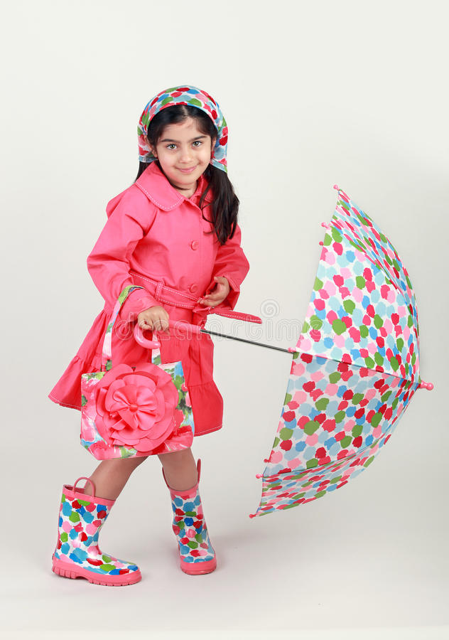 Fashion show. Little girl wearing a rain coat, scarf with matching purse and and holding an umbrella stock photo