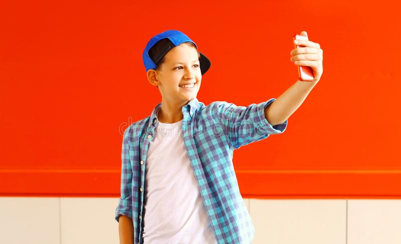 Fashion smiling cool teenager boy is taking picture self portrait. On a smartphone stock image