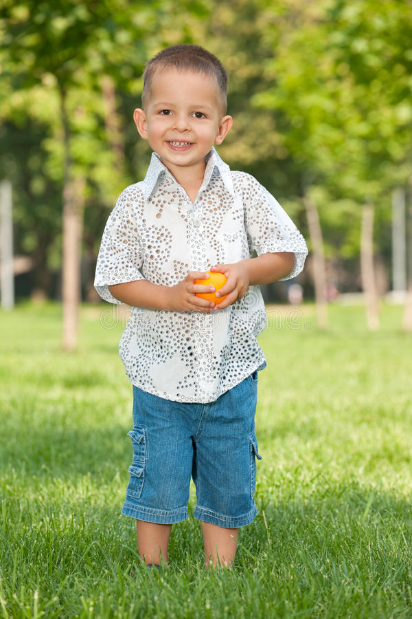 Fashion smiling little boy in the park royalty free stock photos