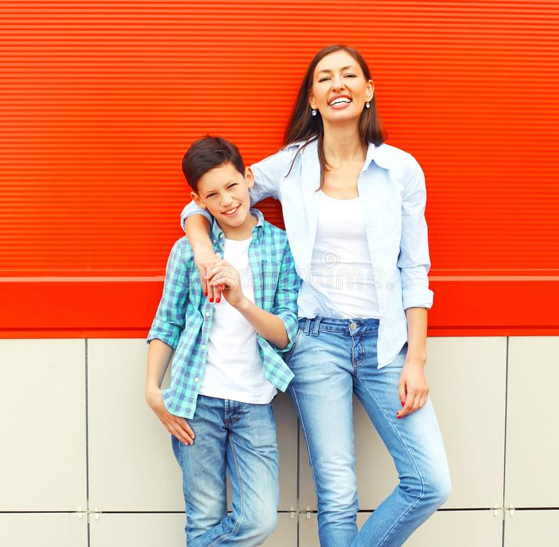 Fashion smiling mother with son teenager together on red royalty free stock photography