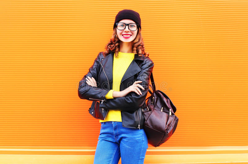 Fashion smiling woman with bag wearing black hat, rock jacket over colorful orange background. Fashion smiling woman with bag wearing a black hat, rock jacket royalty free stock photo