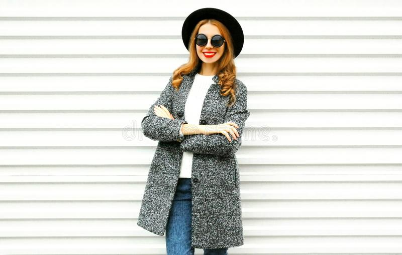 Fashion smiling woman in gray coat, black round hat posing royalty free stock photo