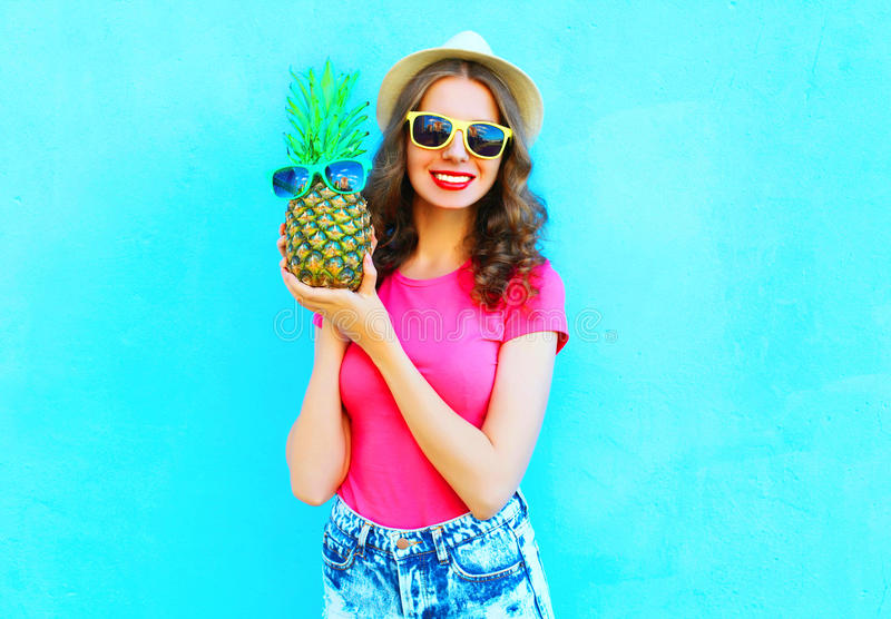 Fashion smiling woman with pineapple sunglasses wearing summer hat having fun over colorful blue stock photography