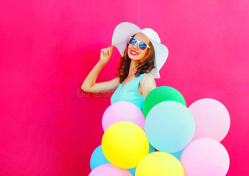 Fashion smiling young woman with an air colorful balloons is having fun on pink background stock image