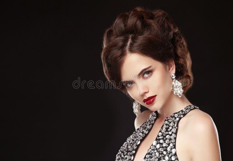 fashion smycken isolerat på vit elegant frisyr Röd kantmakeup Den attraktiva brunetten i lyx prydde med pärlor svart klänningisol royaltyfria foton