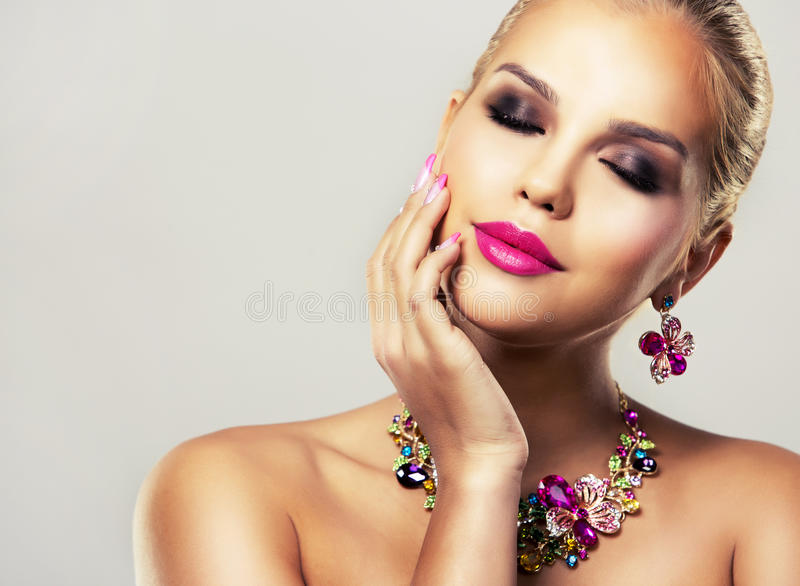 Fashion spring summer blond woman with perfect skin. Beautiful woman with dark makeup and pink lipstick posing on light background wearing flower spring and stock photos