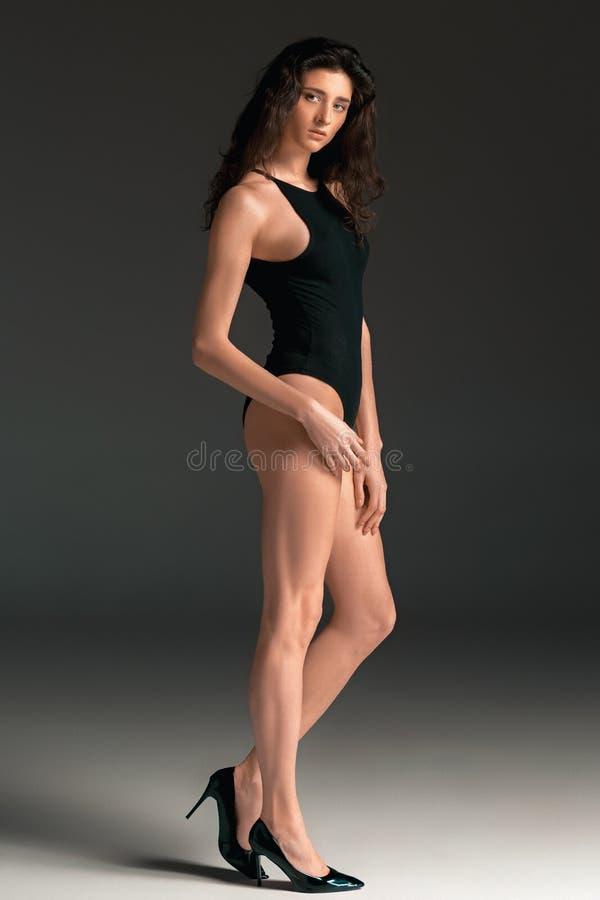fashion ståendekvinnan Härlig barnmodell i en svart baddräkt Studioskott, grå bakgrund royaltyfria foton