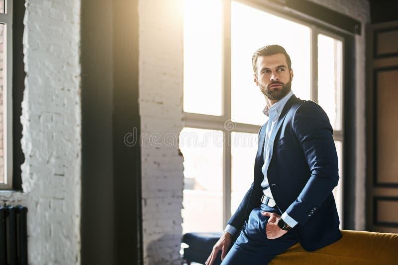 fashion ståenden Den unga skäggiga lyckade affärsmannen i stilfull dräkt står på kontoret och tänker omkring arkivfoto