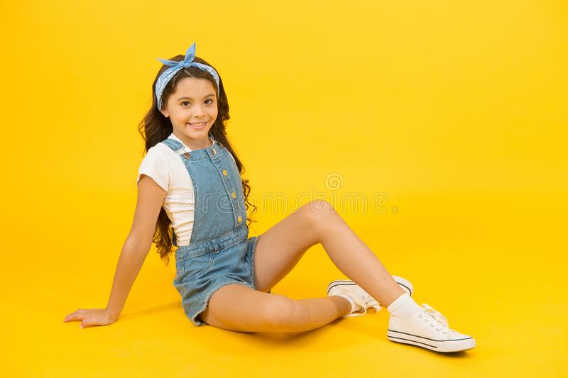 A fashion statement. Fashion look of small vogue model. Adorable girl in fashion wear on yellow background. Fashionable. Little child relax in casual fashion stock photography