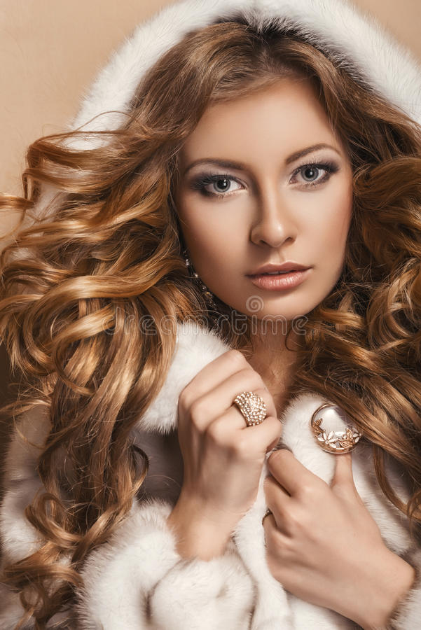Fashion studio photo of beautiful young model with long curly hair. Jewelry. Hairstyle. Vogue Style. stock image