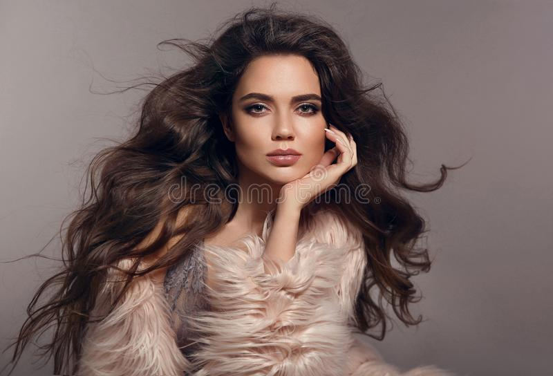 Fashion studio photo of gorgeous brunette woman with long h. Ealthy hair and evening makeup posing with pink fur coat on gray background. Fashionable girl stock image