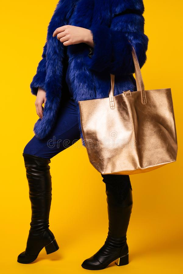 Fashion studio photo of gorgeous woman wears luxurious blue fur coat, with golden bag stock photo