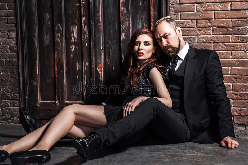 Fashion studio photo of sexy  couple of ginger woman and blonde man dressed wearing classic style, sitting on the flor royalty free stock photography