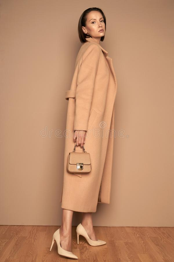 Fashion beautiful lady in beige coat stock photography