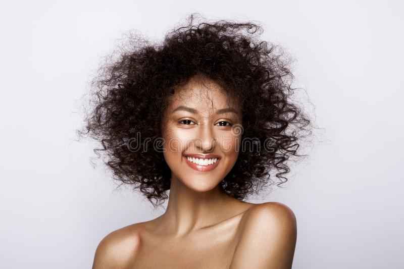 Fashion studio portrait of beautiful african american woman with perfect smooth glowing mulatto skin, make up stock photography