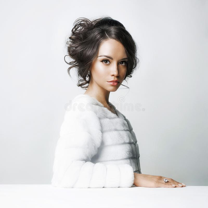 Beautiful woman with elegant hairstyle in white fur coat stock image