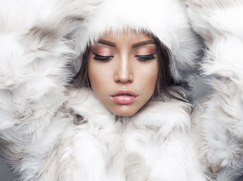 Beautiful woman in white fur coat and fur hat. Fashion studio portrait of beautiful lady in white fur coat and fur hat. Winter beauty in luxury. Fashion fur stock photo