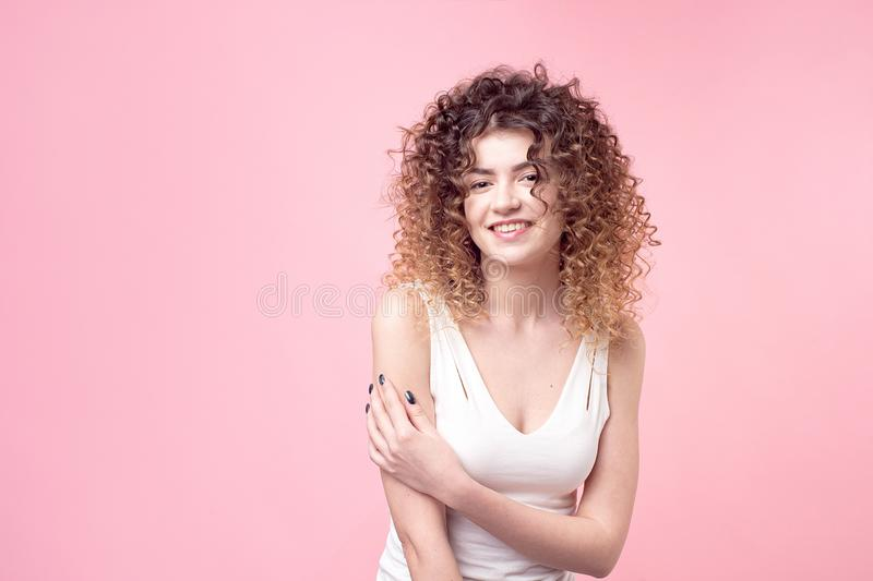 Fashion studio portrait of beautiful smiling woman with afro curls hairstyle isolated over pink background . Fashion and royalty free stock photo