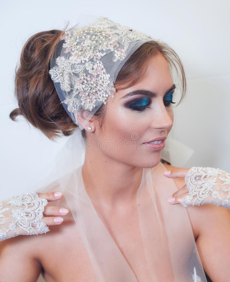 Fashion studio portrait of beautiful young bride with make up and in elegant gloves stock photography