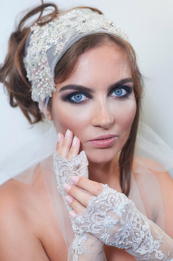Fashion studio portrait of beautiful young bride with make up and in elegant gloves royalty free stock photos