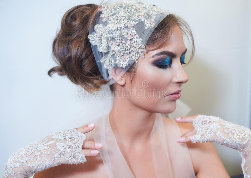 Fashion studio portrait of beautiful young bride with make up and in elegant gloves royalty free stock photography