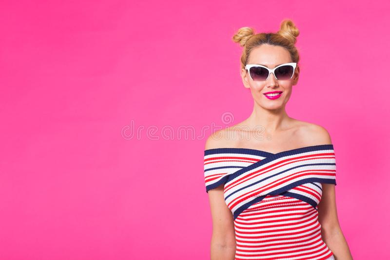 Fashion studio portrait of glamour girl, cute emotions, stylish hipster clothes sunglasses on pink background with royalty free stock photography