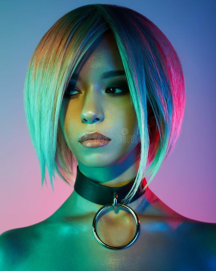 Asian woman in neon light. Beautiul blonde in night club stock image