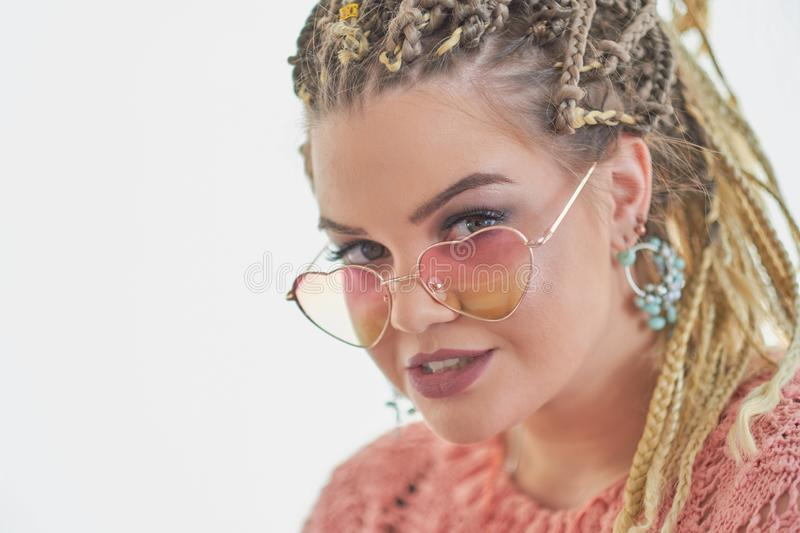 Fashion studio portrait of pretty young hipster blonde woman with bright sexy make up and glasses, White wall background royalty free stock image