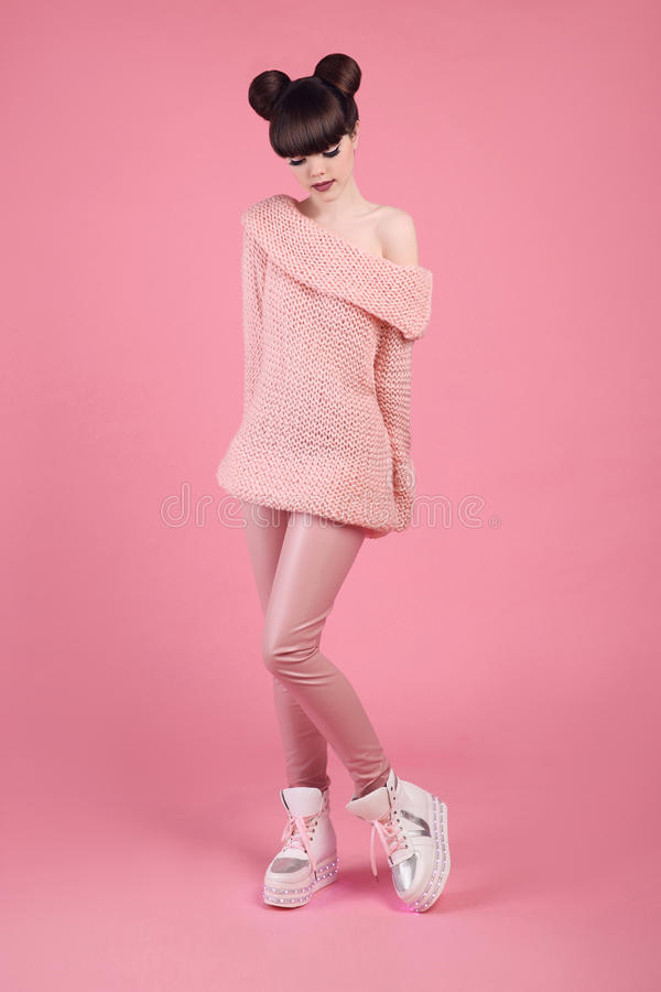 Fashion studio teen look style in boot shoes. Fashionable young. Girl wears wool jumper and leather pants posing isolated on pink background royalty free stock image