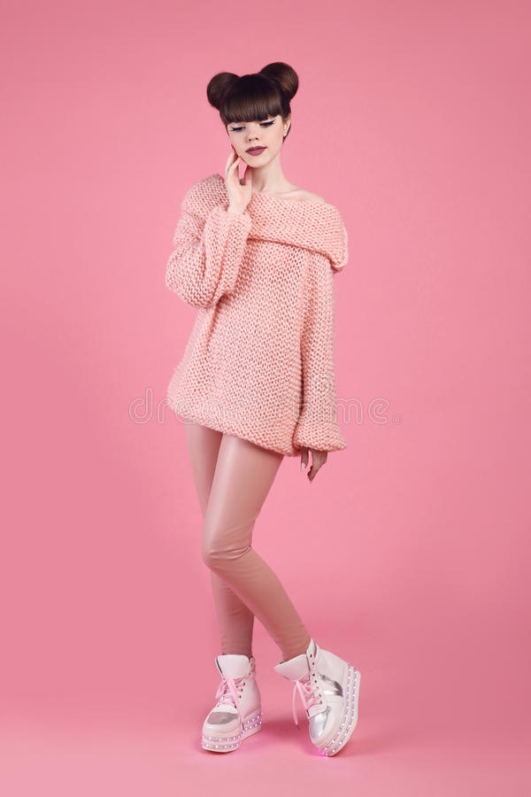 Fashion studio teen look style in boot shoes. Fashionable young. Girl wears wool jumper and leather pants posing isolated on pink background stock image
