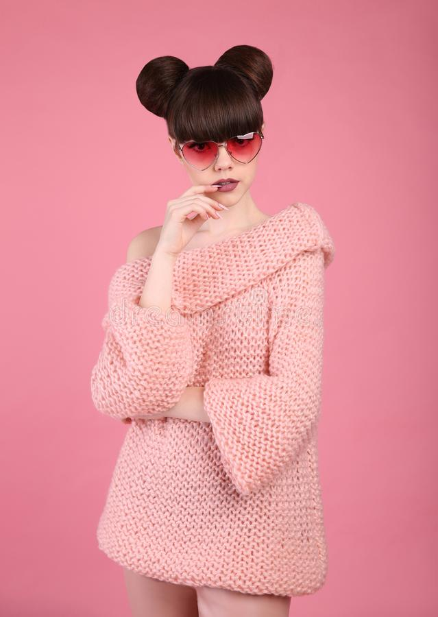 Fashion studio teen look style in knitted sweater. Fashionable y. Oung girl wearing wollen pullover and leather pants posing on pink background royalty free stock photos