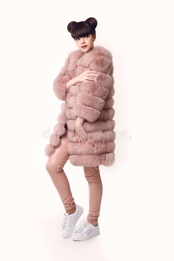 Fashion studio teen look style in pink fur coat and sneakers shoes. Fashionable young girl with ears hairstyle wears leather pant royalty free stock photography