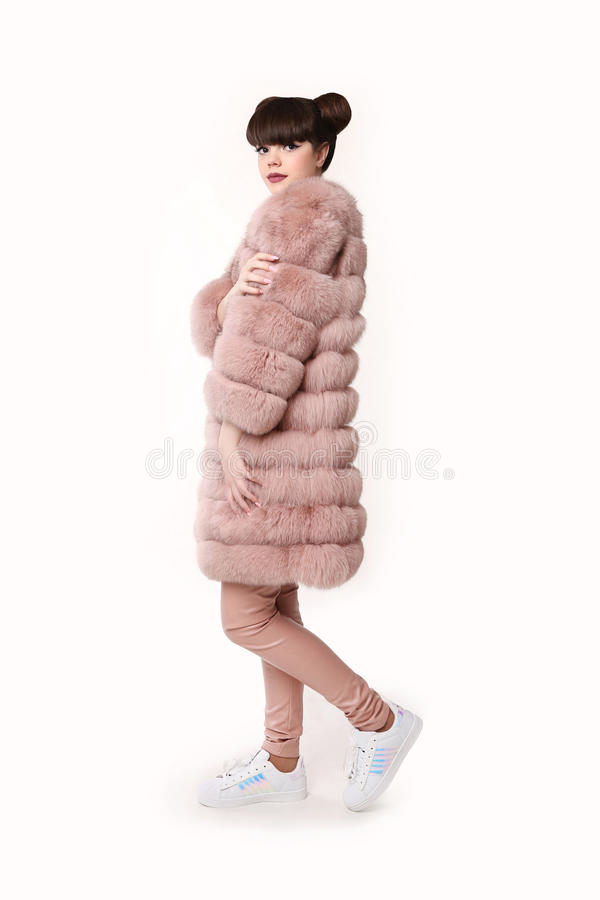 Fashion studio teen look style in pink fur coat and trendy shoes. Fashionable young girl with ears hairstyle wears leather pants posing isolated on white royalty free stock photography