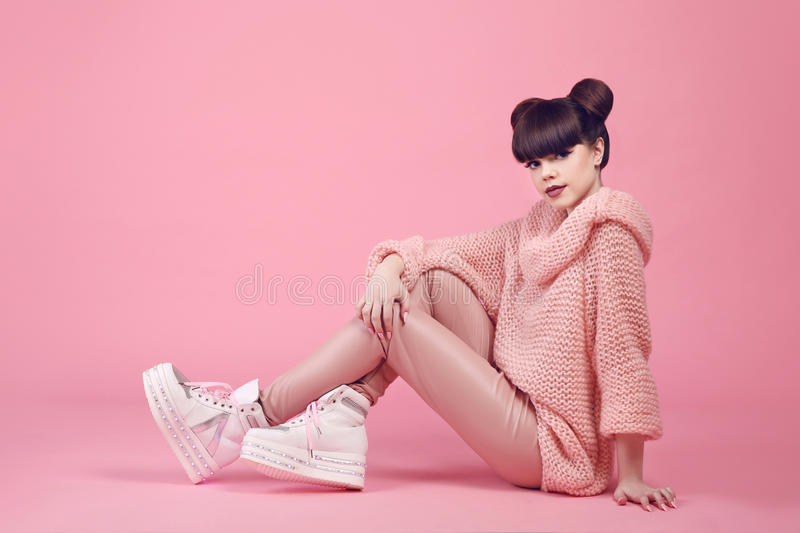 Fashion studio teen look style in shoes. Fashionable young girl. Wears in wool sweater and leather pants sitting on the floor isolated on pink background stock photography