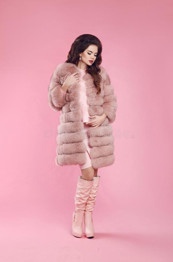 Fashion style attractive woman in fur coat and leather high boot stock photo