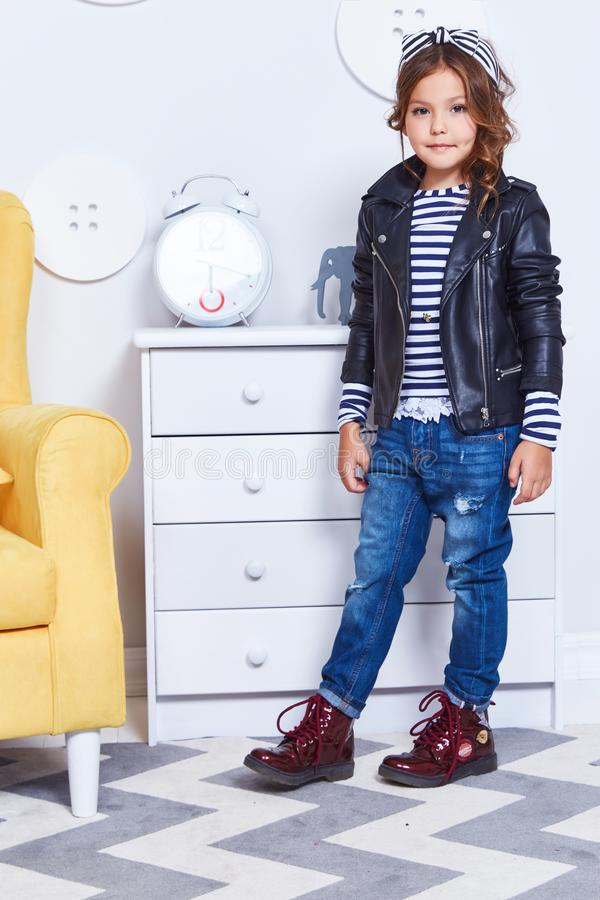 Fashion style clothes for child small little girl wear strip t-shirt denim jeans lather jacket boots hat bow cute pretty face cur stock images