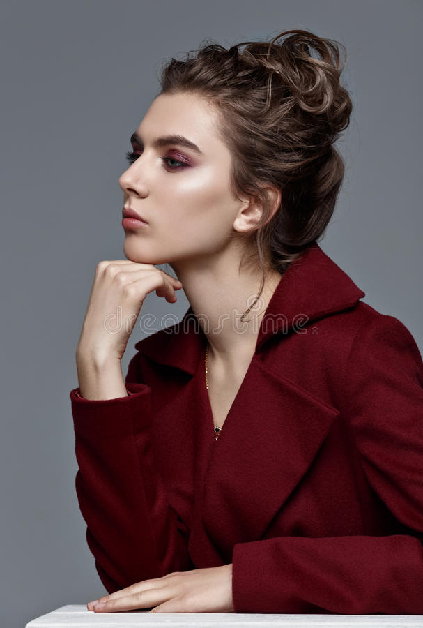 Fashion style model in burgundy coat and art accessories, posing. In the studio on blue background stock images