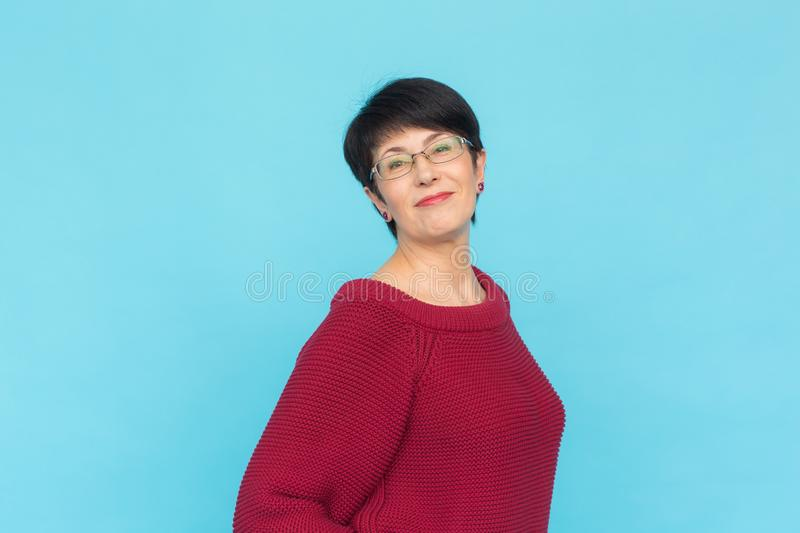 Fashion, style and people concept - smiling pretty middle-aged woman on turquoise background royalty free stock photo