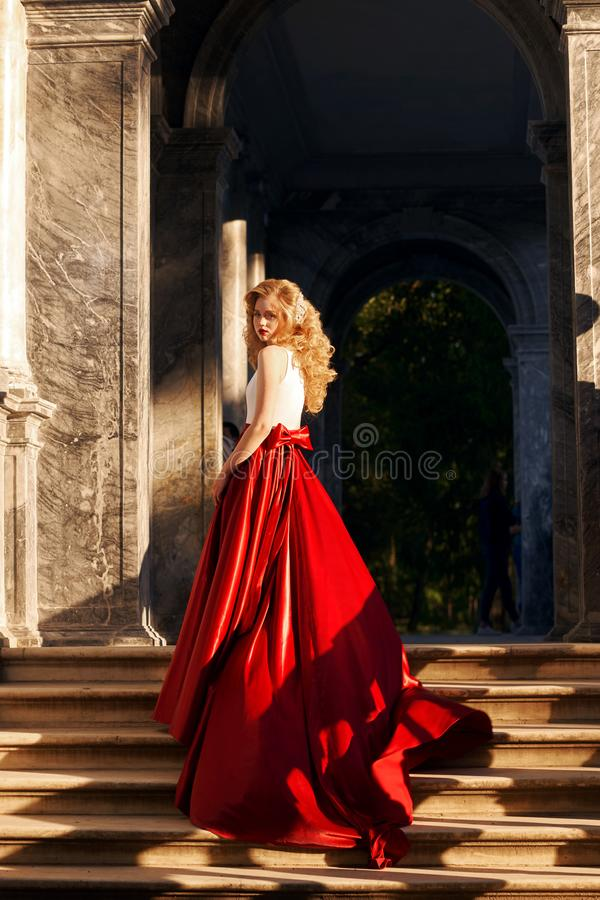 Pretty woman in white dress with red flying skirt in park royalty free stock photos