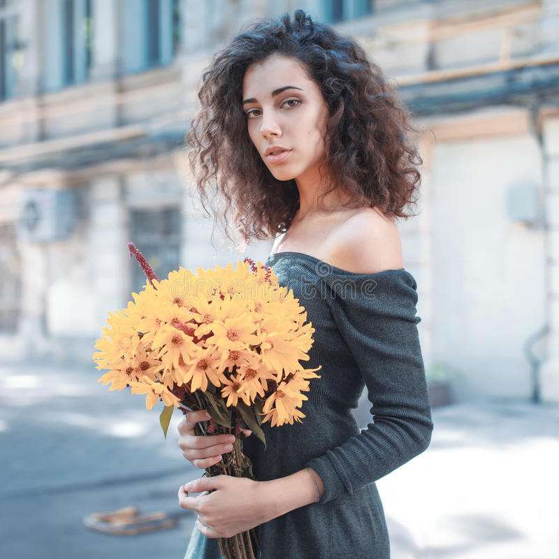 Fashion style photo of a young woman. With yellow flowers on a city background royalty free stock photography