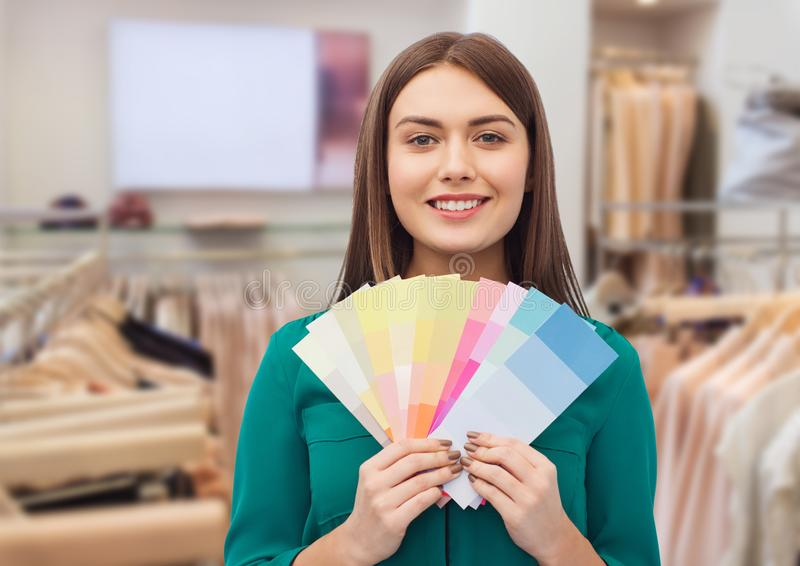 Woman with color swatches at clothing store. Fashion, style and shopping concept - smiling young woman with color swatches or samples over clothing store royalty free stock photos