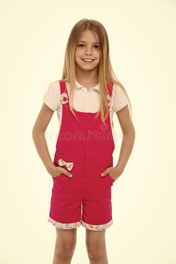 Fashion style and trend. Small girl smile in pink jumpsuit isolated on white. Child smiling with long blond hair. Kid stock images