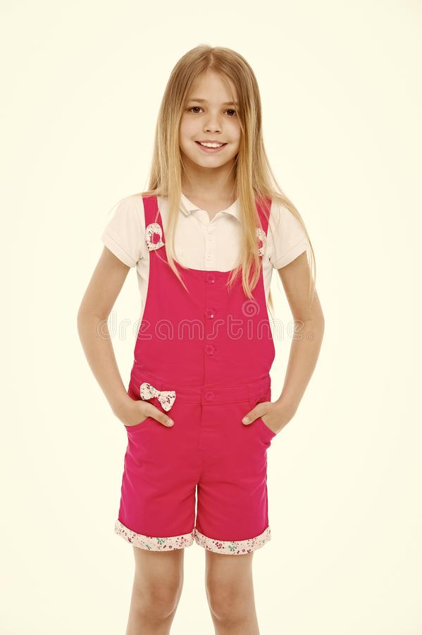 Fashion style and trend. Small girl smile in pink jumpsuit isolated on white. Child smiling with long blond hair. Kid. Model in fashionable overall. Happy stock photo