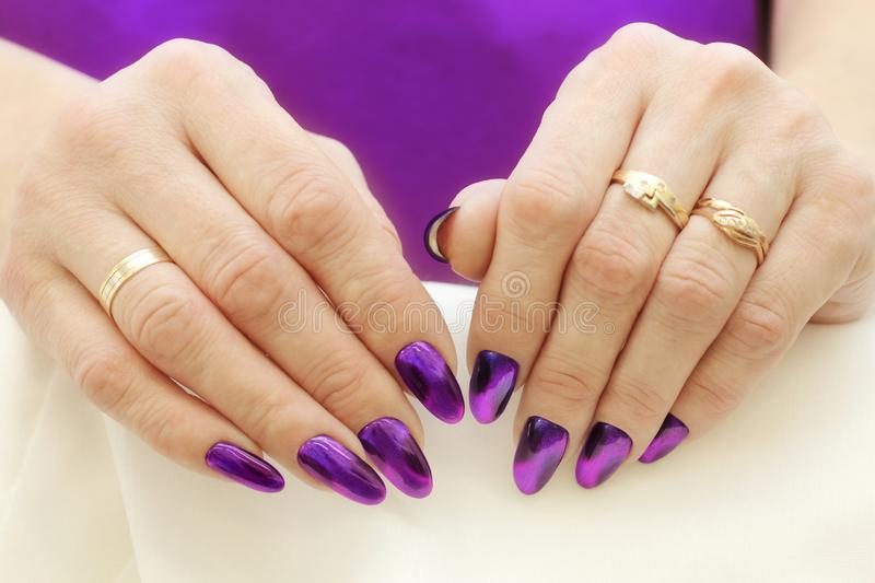 Fashion Style. Violet Nails Manicure. Macro of female hands with nice violet nails manicure