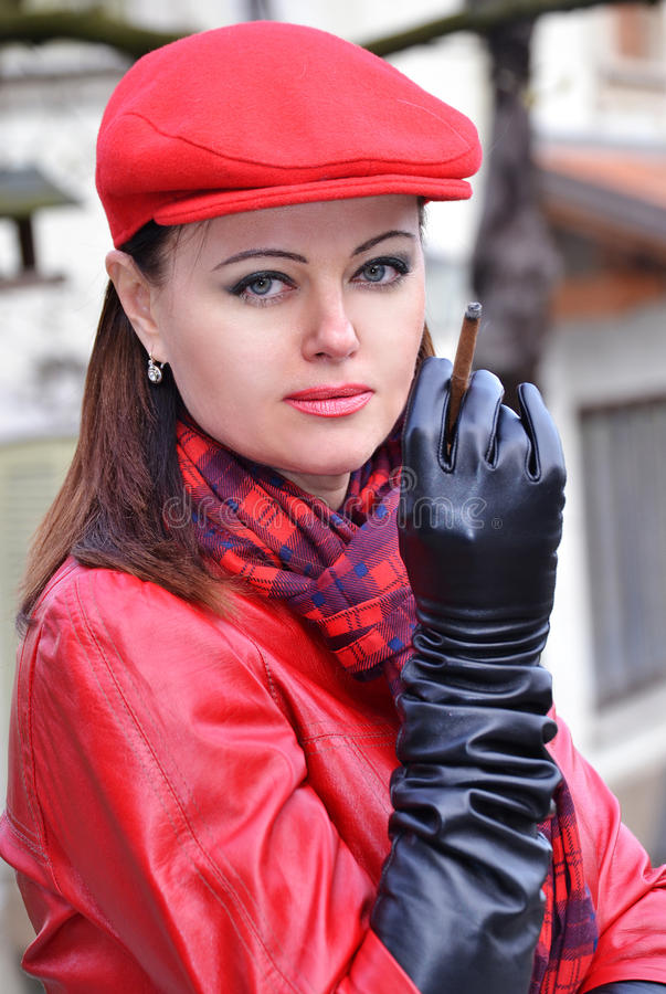 Fashion style woman portrait. Fashion style woman smoking wearing red hat,black gloves and red leather jacket stock images