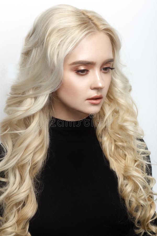 Profile portrait of a woman with curly blonde hairstyle in black jumper, soft make up, isolated on a white background. stock photo